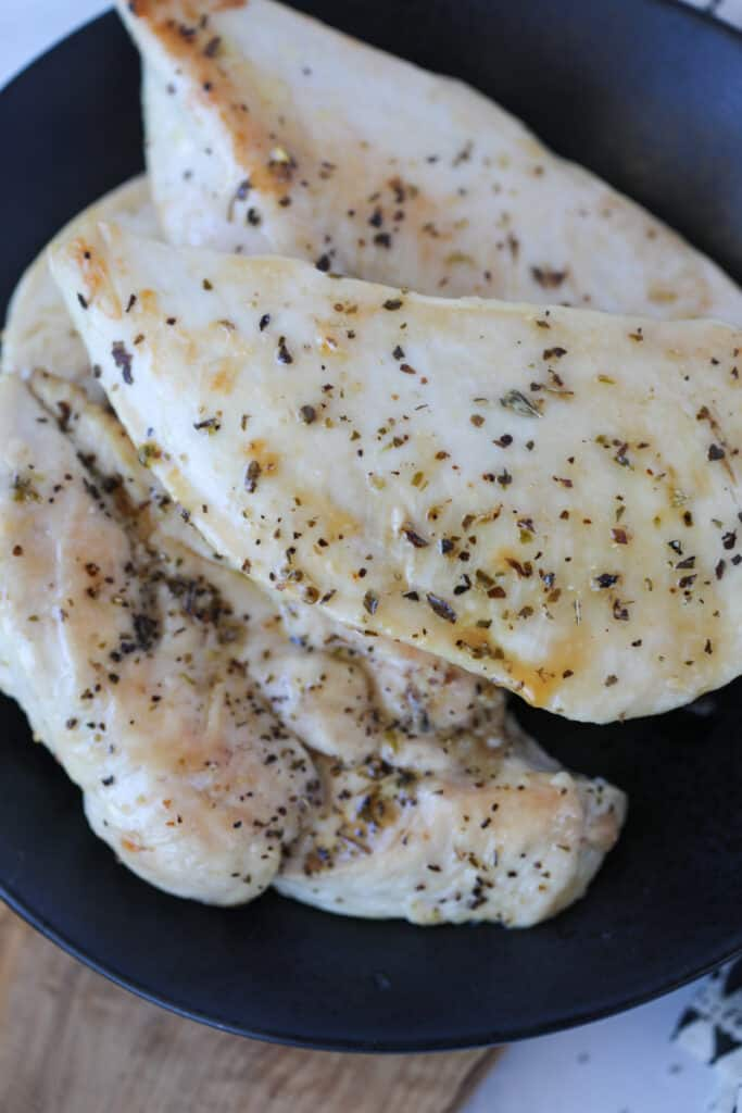 baked thin chicken breast on a black plate after cooking in the oven
