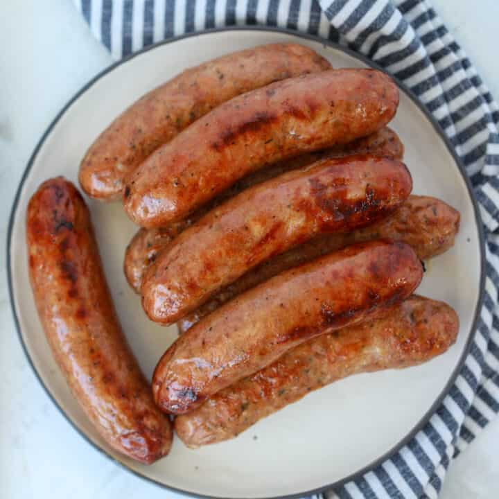 chicken sausage in air fryer roasted on a white plate after cooking