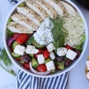 greek salad meal prep in a bowl with tzaziki sauce and cauliflower rice