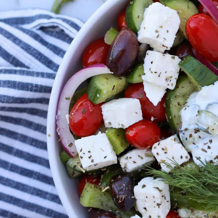 greek tomato cucumber salad in a white bowl
