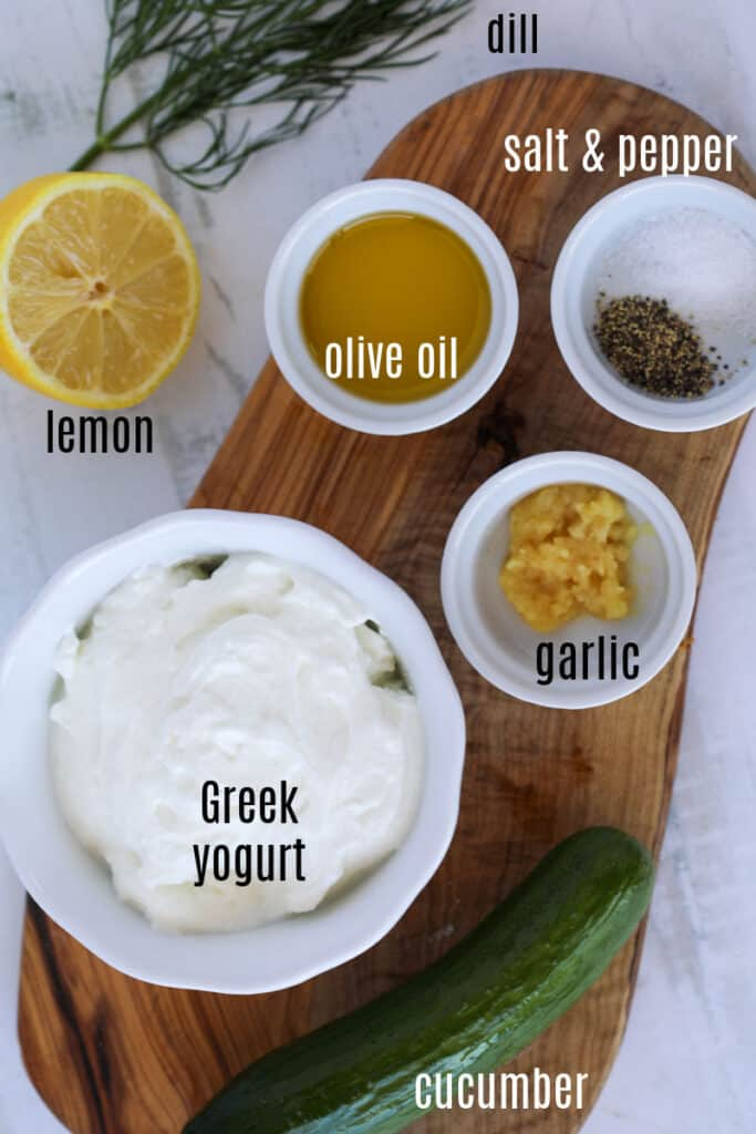 the ingredients for tzatziki sauce on a cutting board