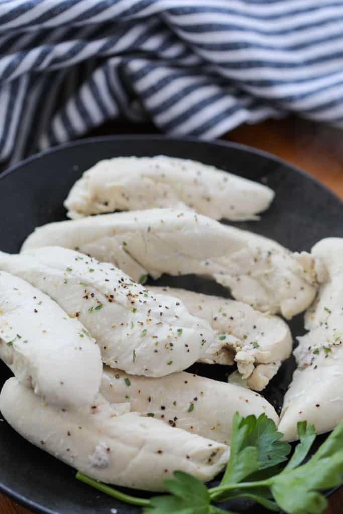 boiled chicken tenderloins on a black plate after simmering on the stovetop