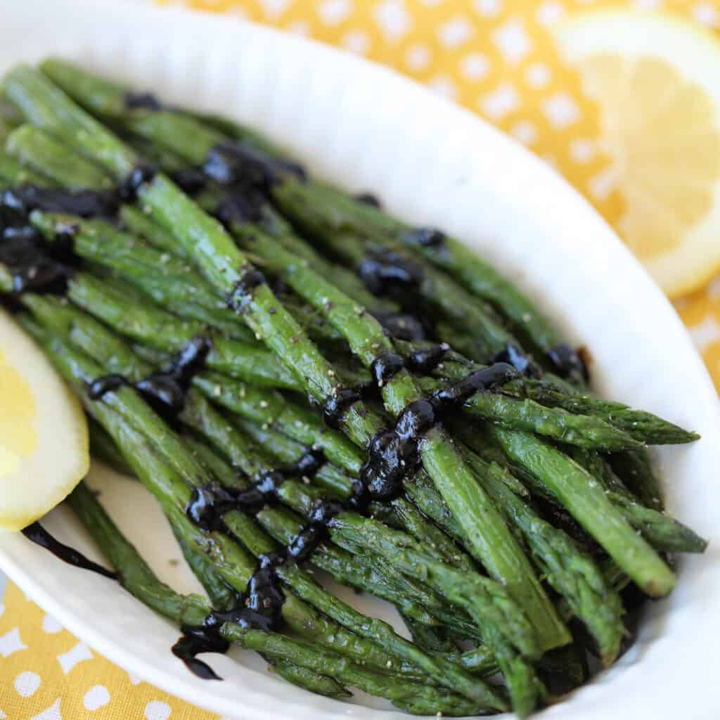 cooking frozen asparagus in an air fryer in a serving dish with lemon and balsamic