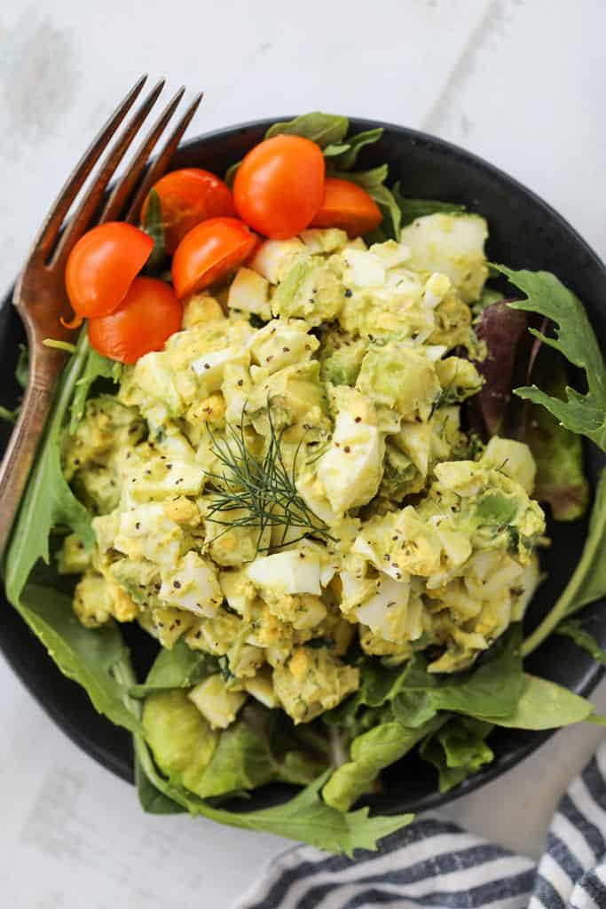 egg and avocado salad on a black plate