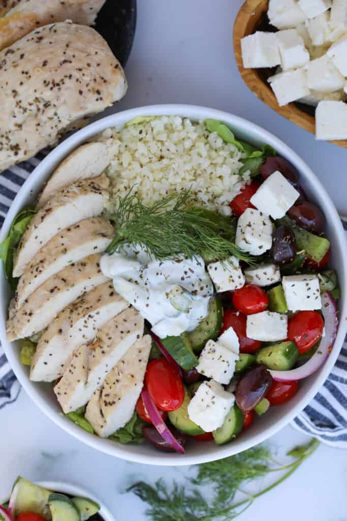 greek salad bowl with chicken in a white bowl