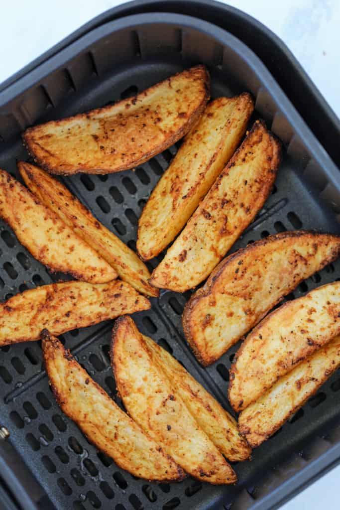 potato wedges in air fryer basket after cooking